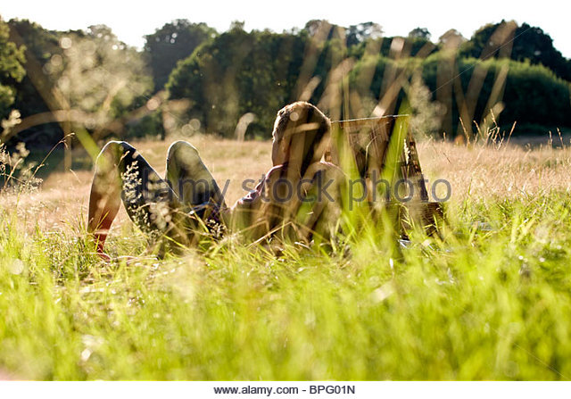 A young man sitting on the grass, enjoying the sun - Stock Image