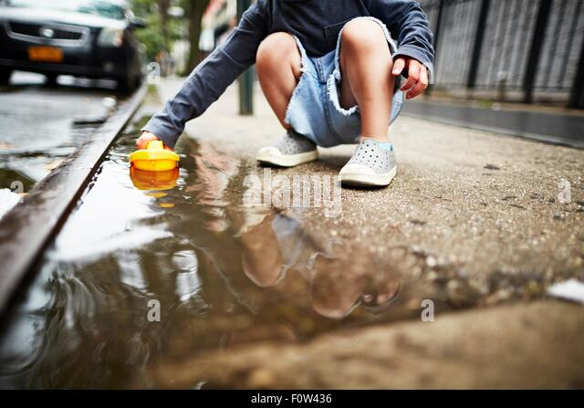 Boy playing with toy boat on water on pavement - Stock-Bilder