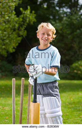 Boy (6-8) playing cricket, smiling, portrait - Stock Image