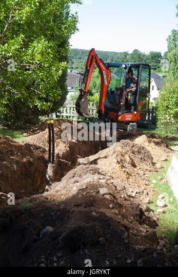 EXCAVATOR in garden digging for mountain heath 2017 - Stock Image