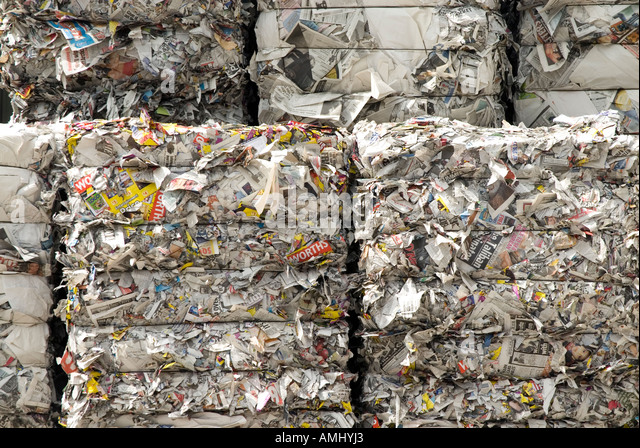 Bundles of returned newspapers at paper recycling facility England UK - Stock Image