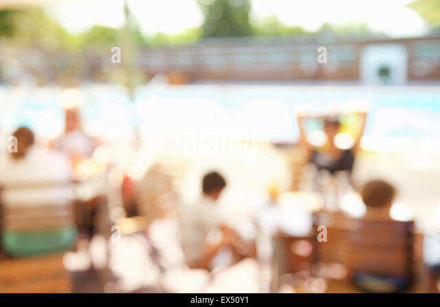 Defocused Image of People Relaxing at Cafe by Swimming Pool - Stock Image
