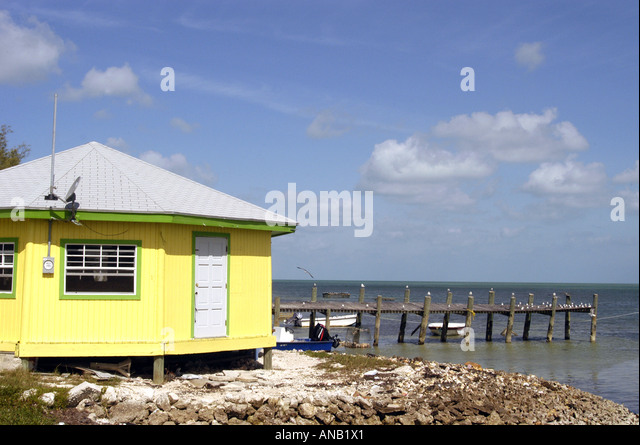 Bahamas Bahamian mounds of conch shells yellow building at beach - Stock Image