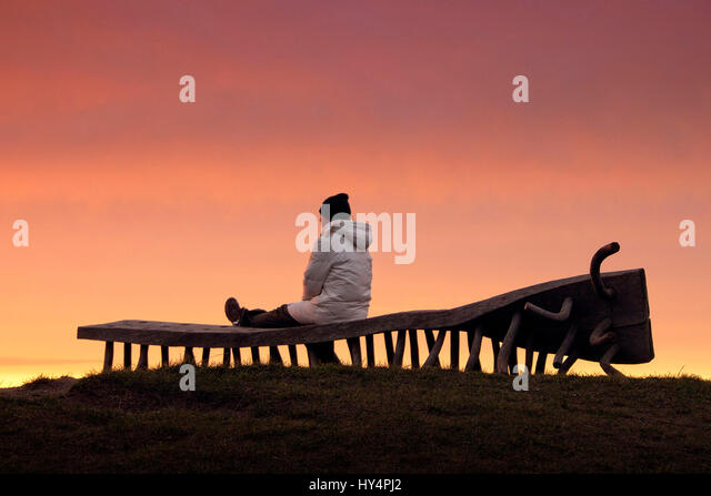 Walker sitting on a bench and artistically designed view to the sunset over the sea - Stock-Bilder