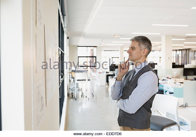 Pensive architect reviewing plans on wall - Stock Image