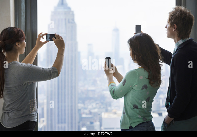 Urban lifestyle Three people standing on an observation deck using their phones to take images of the view over - Stock Image