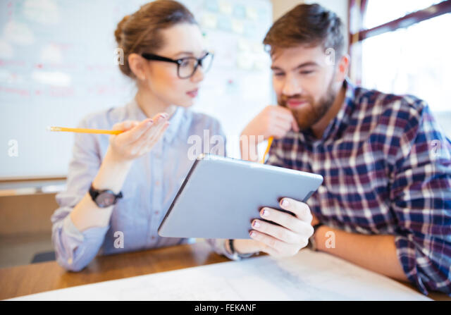 Two business people working with tablet computer in office. Focus on tablet computer - Stock Image
