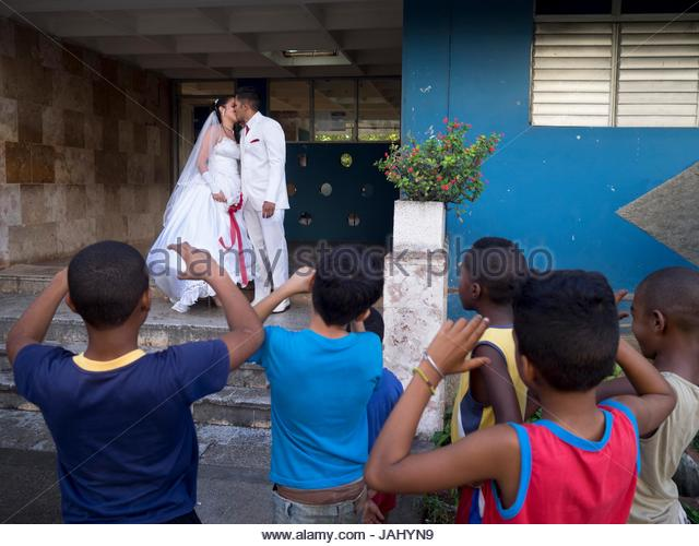 A group of boys pretend to take photos of newlyweds on the Calle 20 de Mayo. - Stock Image
