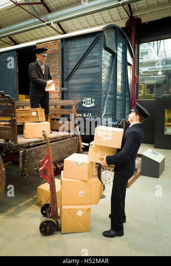 A GWR porter handling goods packages at the STEAM museum in Swindon UK - Stock Image