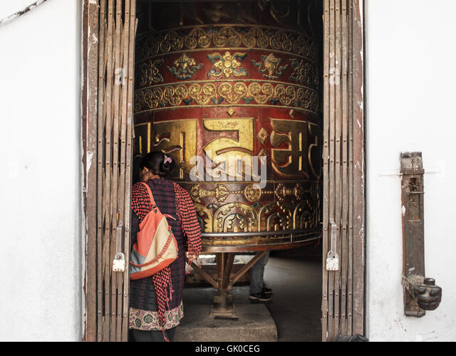 A woman turns a prayer wheel in Boudhanath Temple in Kathmandu, Nepal. - Stock Image