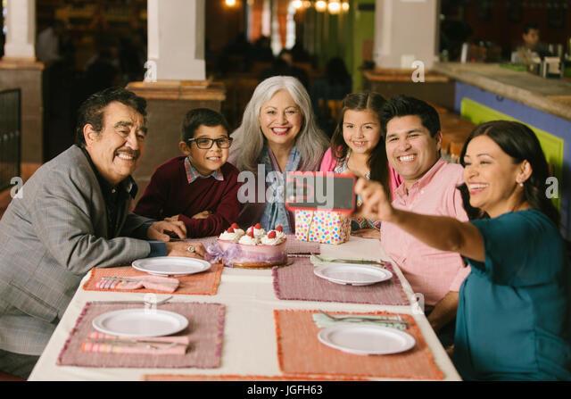 Family celebrating birthday posing for selfie in restaurant - Stock Image