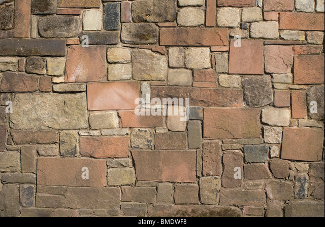 A solid stone wall made of sandstone limestone and granite. - Stock-Bilder