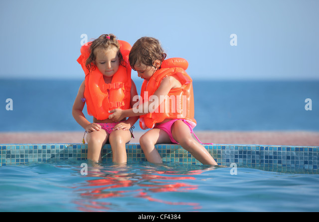 two little girls in lifejackets sitting on ledge pool on resort - Stock Image