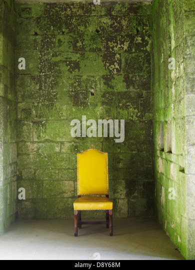 A bright yellow chair against a lichen covered wall. - Stock Image