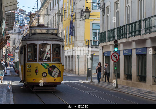 Trams on a street in city center of Lisbon - Portugal. In operation since 1873, it comprises of five urban lines - Stock Image