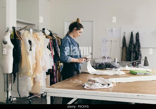 Young female seamstress cutting pattern in fashion studio - Stock Image