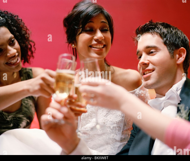 Close up of bride and groom toasting with friends - Stock-Bilder