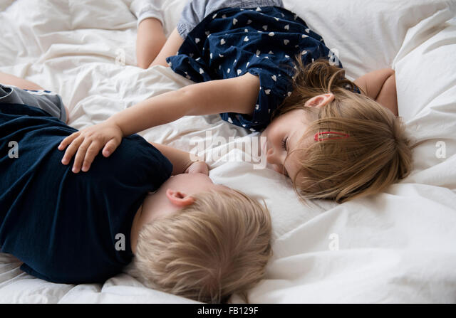 Brother (2-3) with sister (2-3) sleeping on bed - Stock Image