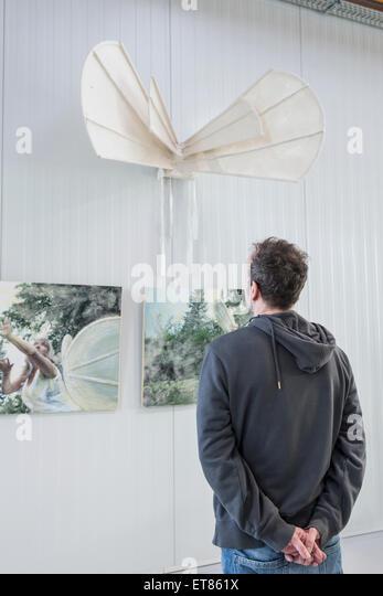 Visitor looking at paintings in an art gallery, Bavaria, Germany - Stock-Bilder