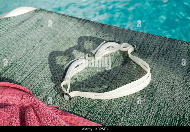 Pair of swimming goggles left on a sun lounger by a pool at Hotel Ninays in Lloret de Mar - Stock Image