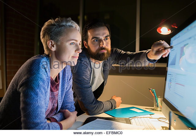 Graphic designers working late at computer in office - Stock Image