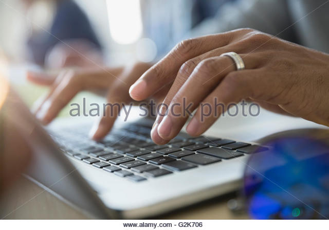 Close up adult education student typing on laptop - Stock Image