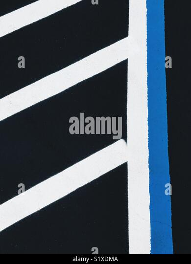 Bold painted white and blue lines on black asphalt in a parking lot. - Stock Image