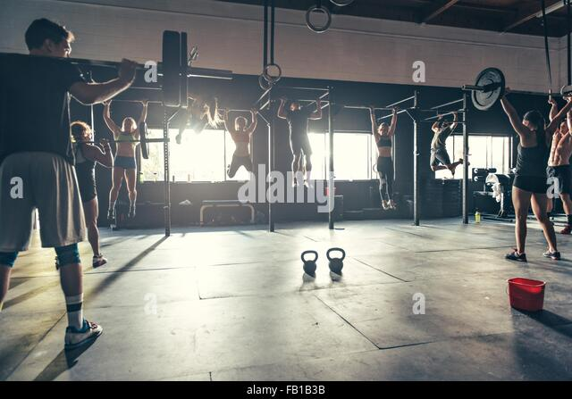 Team training using varied equipment in gym - Stock Image