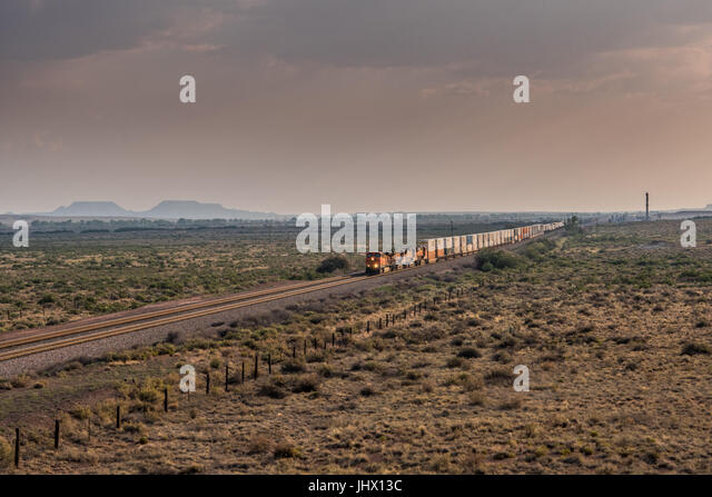 Diagonal View of Train Rolling Across Desert in late afternoon - Stock Image