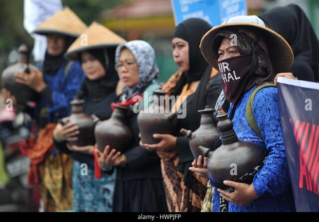 Jakarta, Indonesia. 22nd Mar, 2017. Indonesian activists hold jugs of water during a rally to mark World Water Day - Stock Image