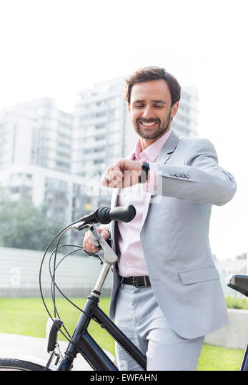 Happy businessman with bicycle checking time outdoors - Stock Image
