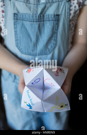 A girl with an Origami Fortune Teller paper game - Stock Image