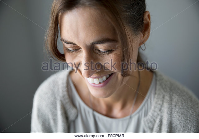 Close up laughing woman looking down - Stock Image