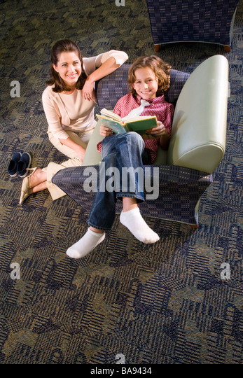 Portrait of elementary school teacher with pupil in library - Stock Image