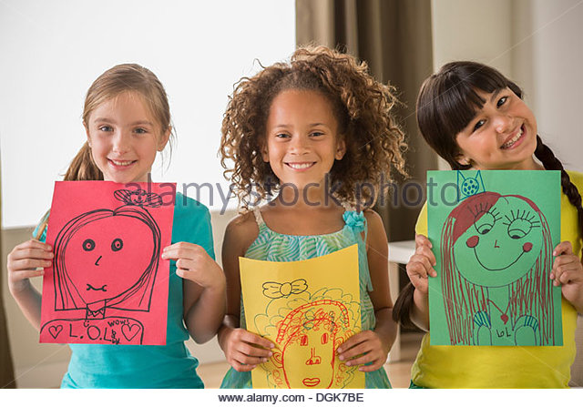 Three girls holding drawings of faces - Stock-Bilder