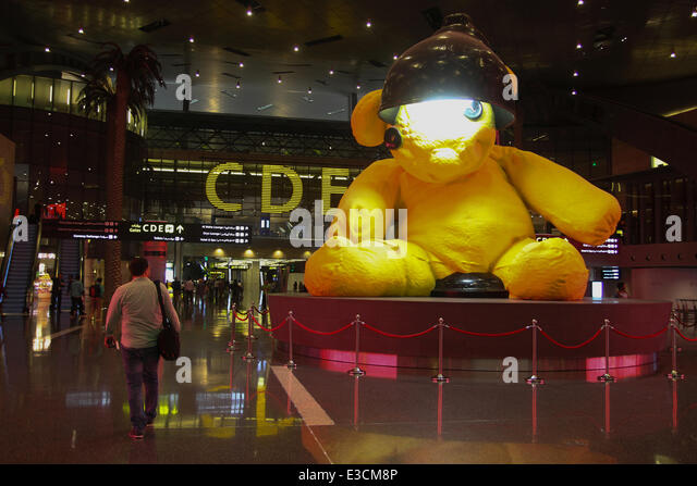 Doha, Qatar, 22nd June, 2014. A passenger seen walking past the Lamp Bear installation by Swis artist Urs Fisher - Stock Image