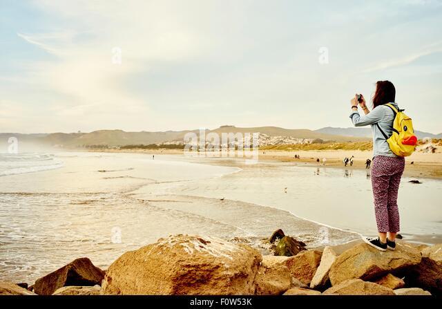 Female tourist photographing sea view on smartphone, Morro Bay, California, USA - Stock-Bilder