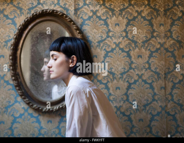 Side View Of Woman Against Mirror At Home - Stock Image