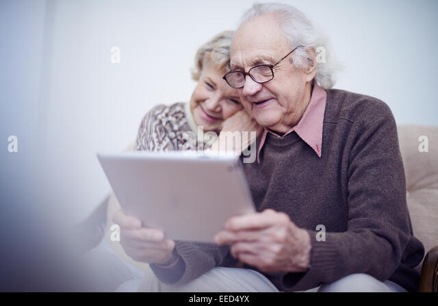 Elderly husband and wife using touchpad - Stock-Bilder