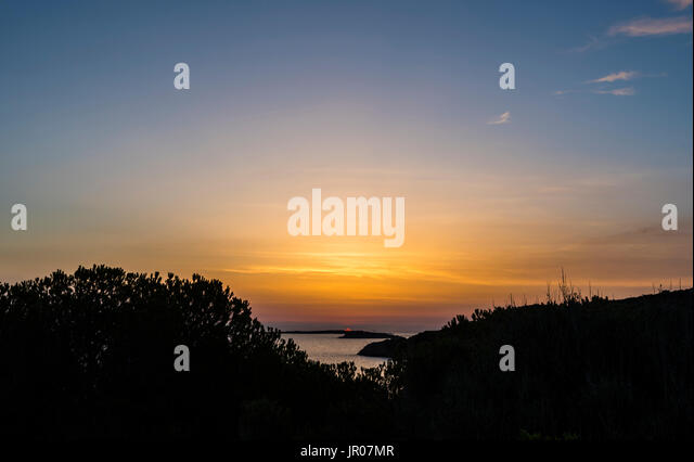 First red light of a fabulous orange sunrise over Sardinia, Italy - Stock Image