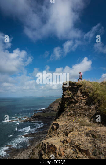 United Kingdom, England, Cornwall, Hiker at High Cliff - Stock Image