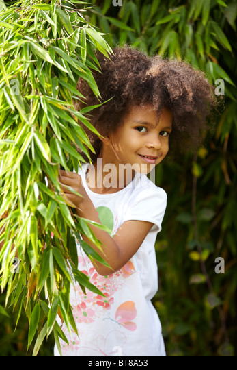 young mixed race girl, child, peeking out from behind bamboo plant in garden in the sunshine. - Stock Image