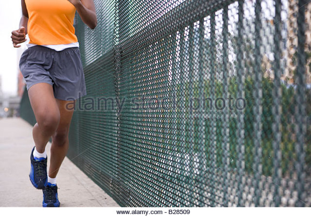 Woman running by fence, low section - Stock Image