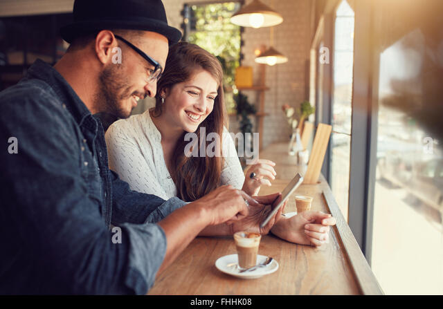 Happy couple in a coffee shop surfing internet on digital tablet. Young man and woman in a restaurant looking at - Stock Image