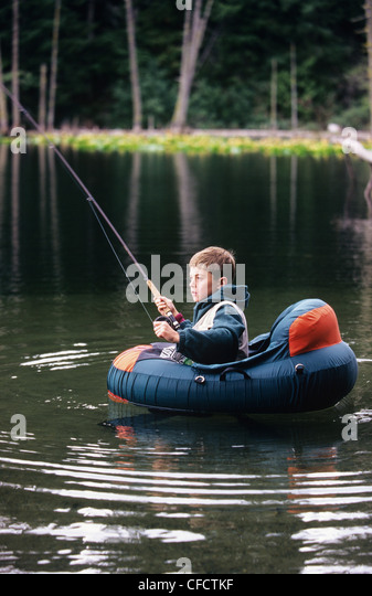 Young boy in inflatable boat stock photos young boy in for Fly fishing float tube