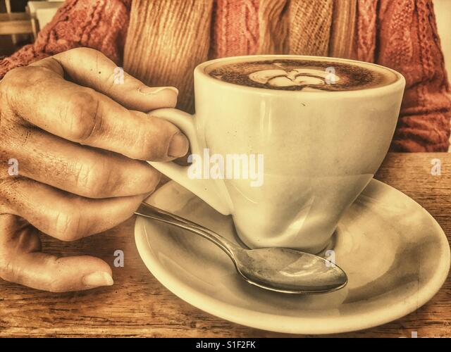 Woman drinking a cappuccino coffee, close up of hand on cup handle - Stock Image