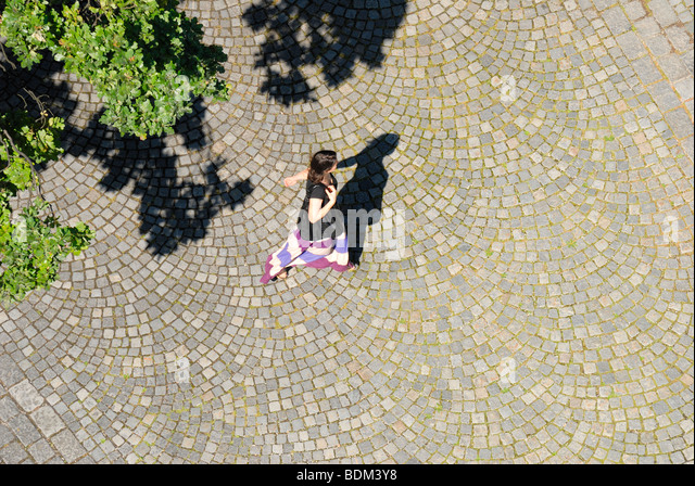 Maribor, Stajerska, Slovenia. Woman walking across typical cobbles. From cathedral tower - Stock-Bilder