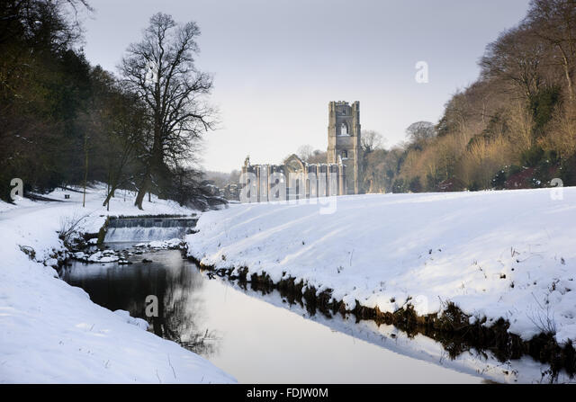 A view along the River Skell in winter towards Fountains Abbey, North Yorkshire, a Cistercian community of monks - Stock-Bilder