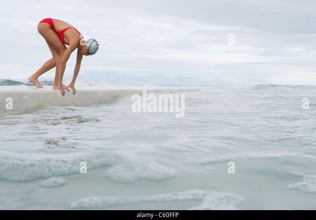 Runner jumping into water from dock - Stock Image