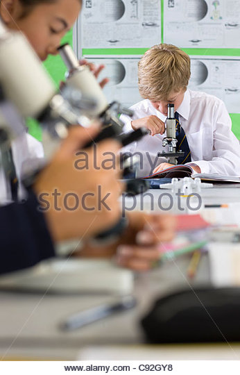 Students using microscopes in science class - Stock Image